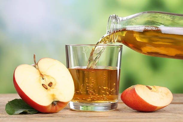 red apple juice pouring into a glass picture